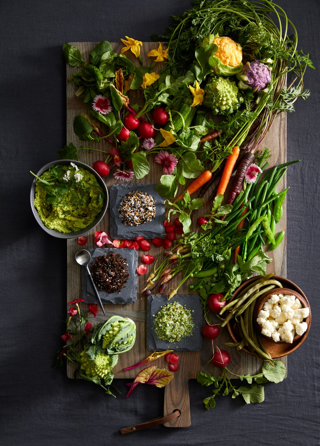 Veggie board with carrots, green beans and radishes along with dips and flavored salts on the side