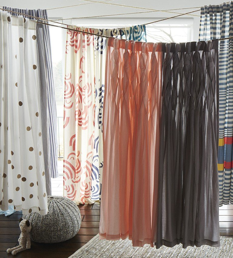 A variety of curtains hang together to show different patterns and colors.