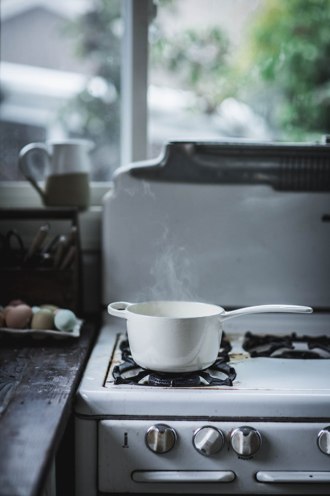 a steaming pot of sauce is cooking on the stovetop in front of a large window