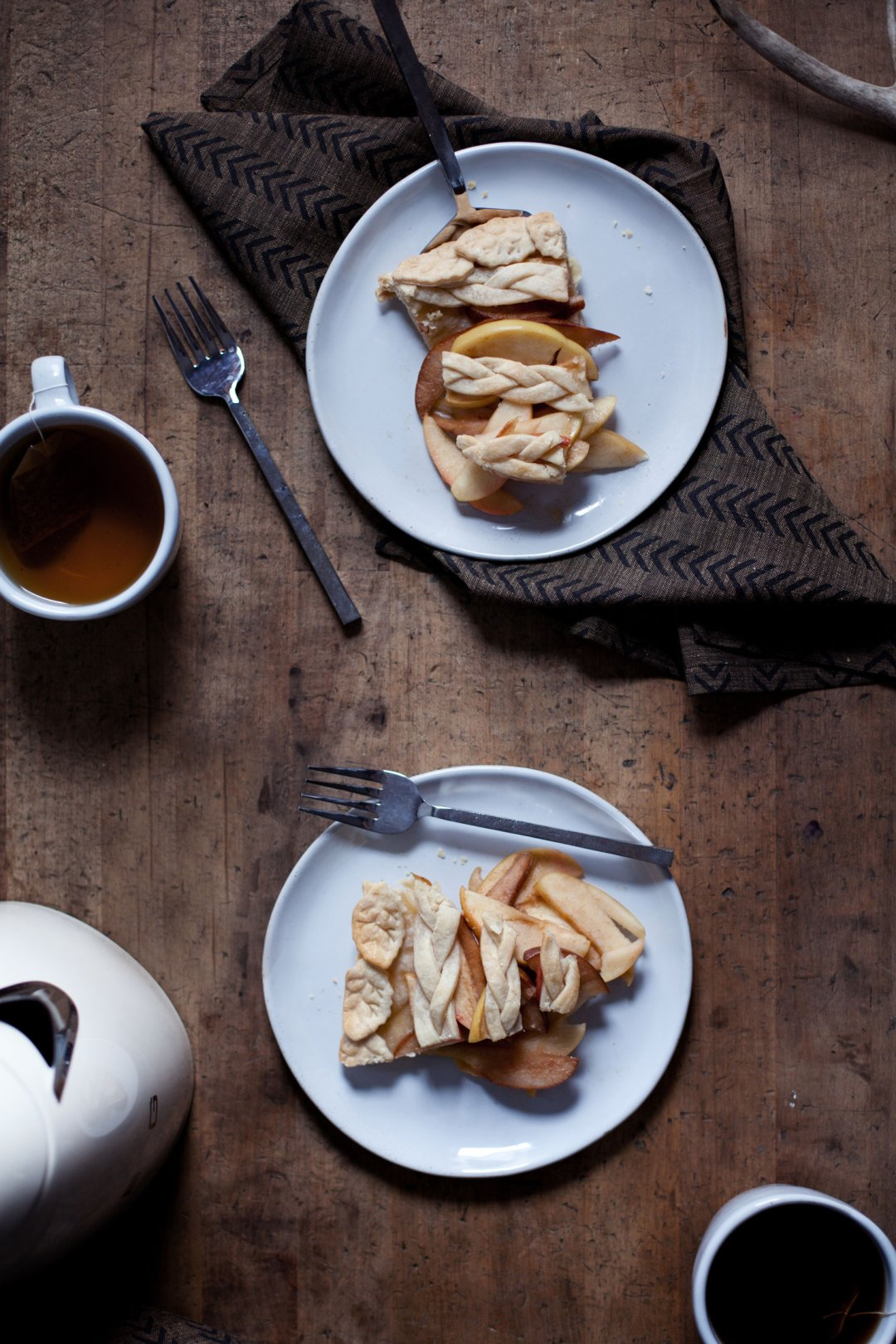 Two slices of apple an pear pie on plates served with tea