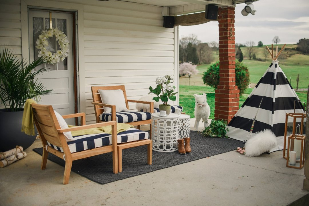 View of front porch makeover with lounge chairs, tables, teepee, lanterns, and plants