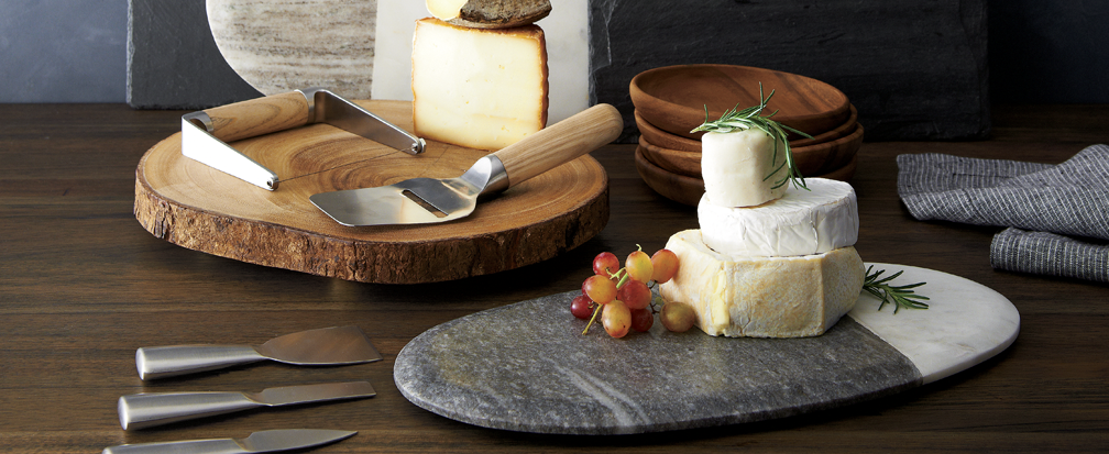 Cheese and grapes on marble and wood cheese platters