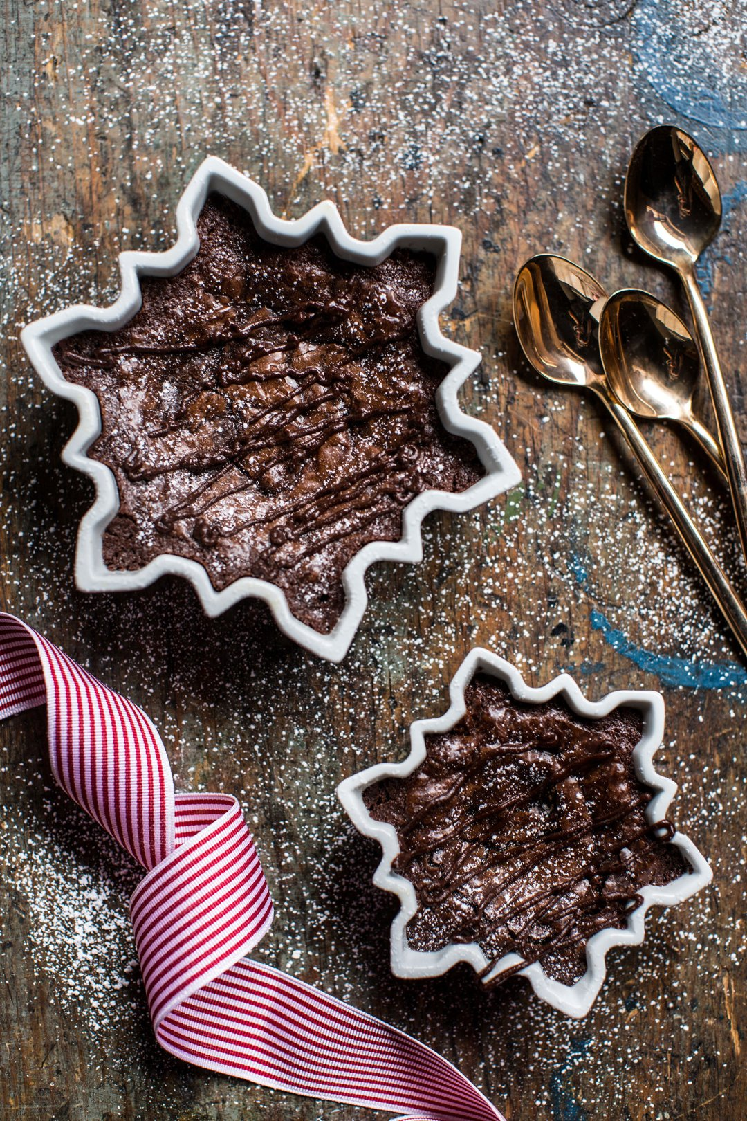 Two chocolate brownie cakes in snowflake-shaped dishes next to a few gold spoons on a wood countertop