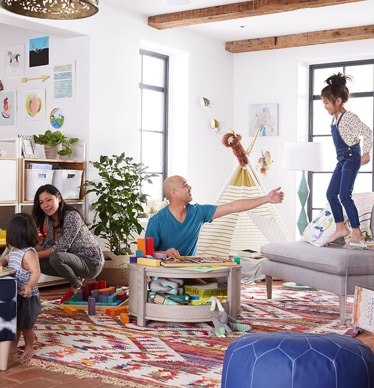 A family plays together in their living room, which has toys and a cozy rug