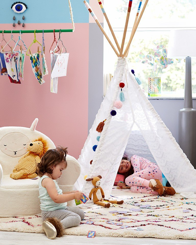 Kids play in a teepee with their stuffed animals.