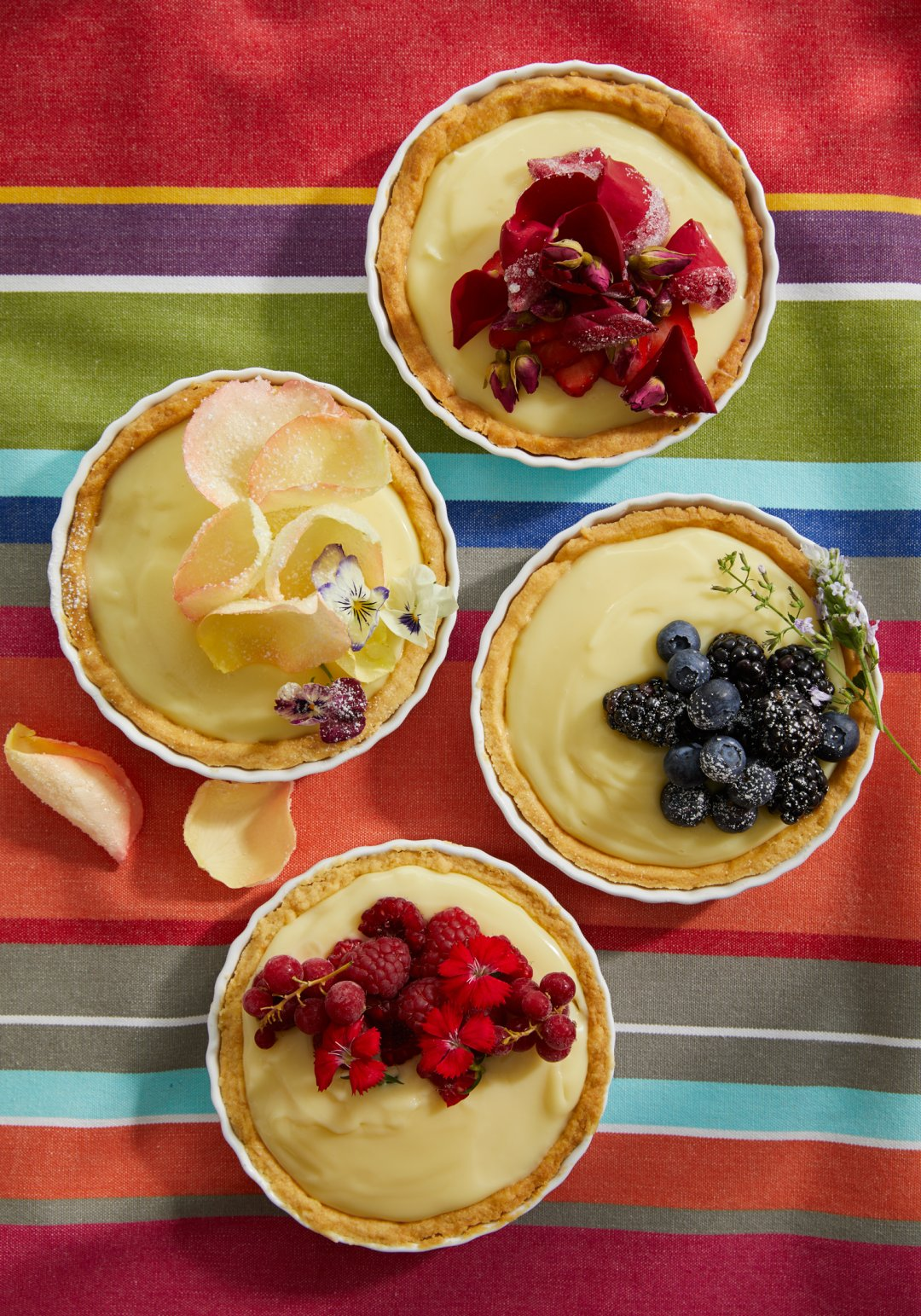 Four mini fruit tartelettes on a bright tablecloth