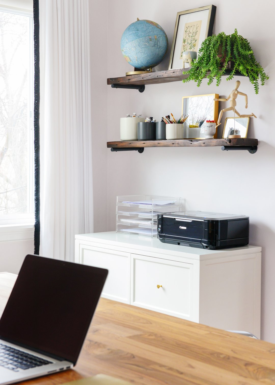 a printer and filing rack sits on a cabinet below two shelves displaying painting supplies, photos, a plant and a globe