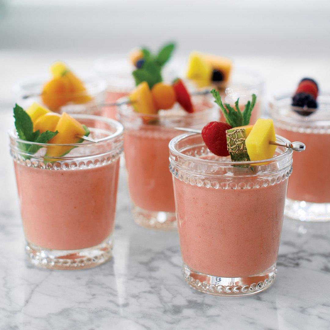 Cantaloupe and raspberry smoothies with fresh fruit garnish