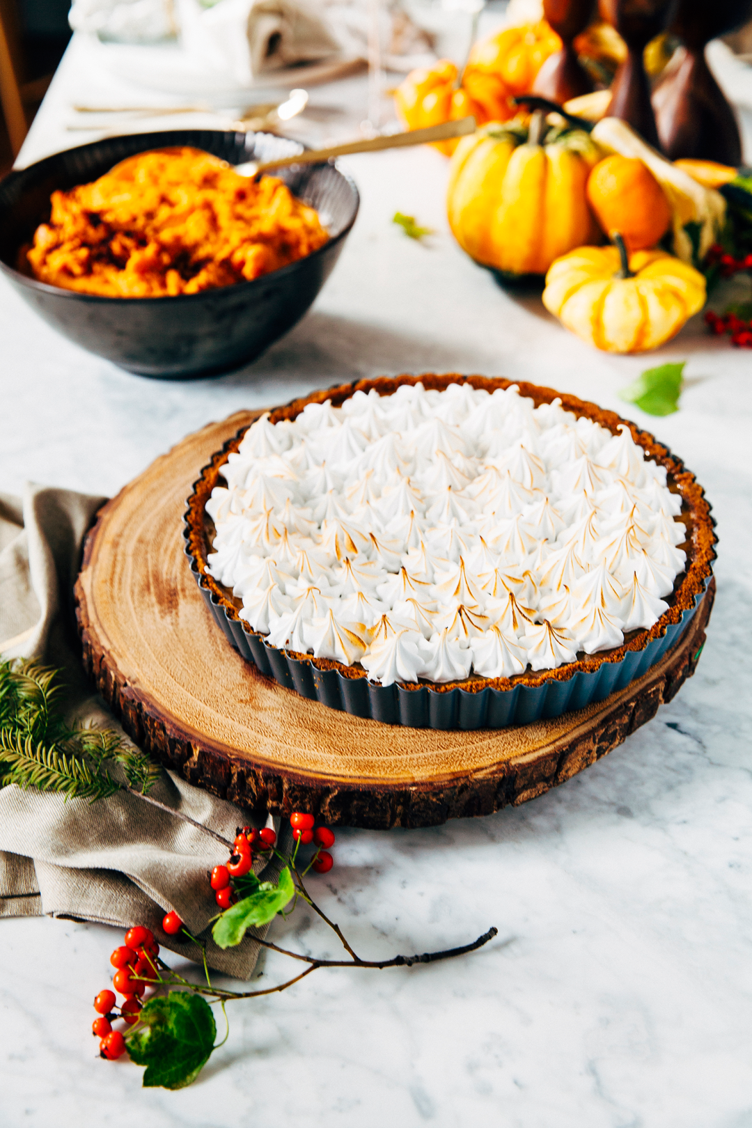 Pumpkin pie with a toasted meringue topping on a wood log serving tray