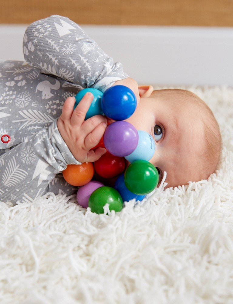 Baby playing with classic wooden toy on a plush carpet.
