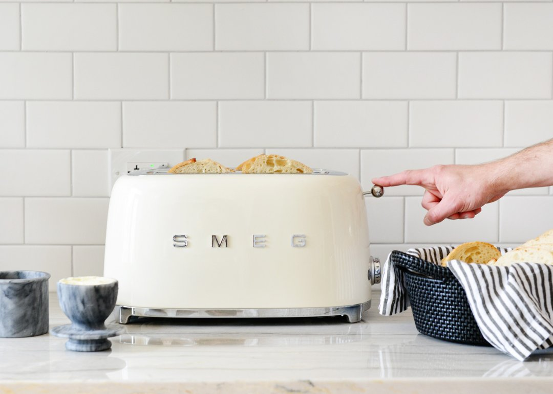 Putting toast into white smeg toaster next to marble butter keeper and black basket filled with bread on a striped napkin