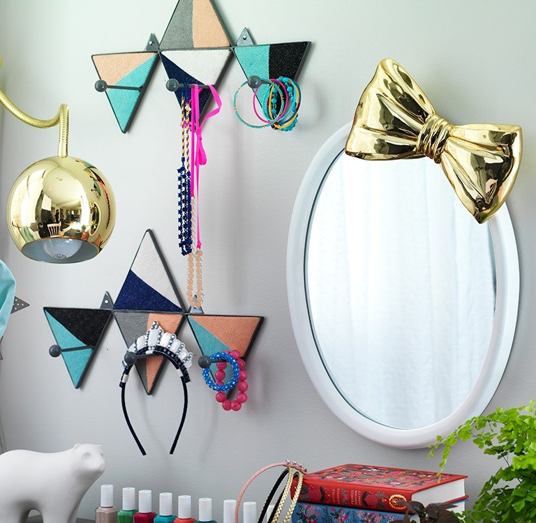 A small desk with mirror and wall hooks for storage.