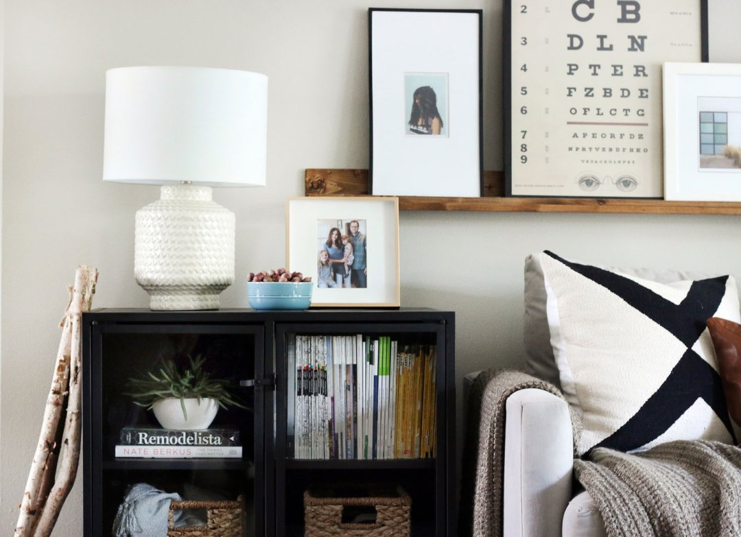 Black modular living room storage tabletop holding a framed photo, white table lamp and bowl of nuts