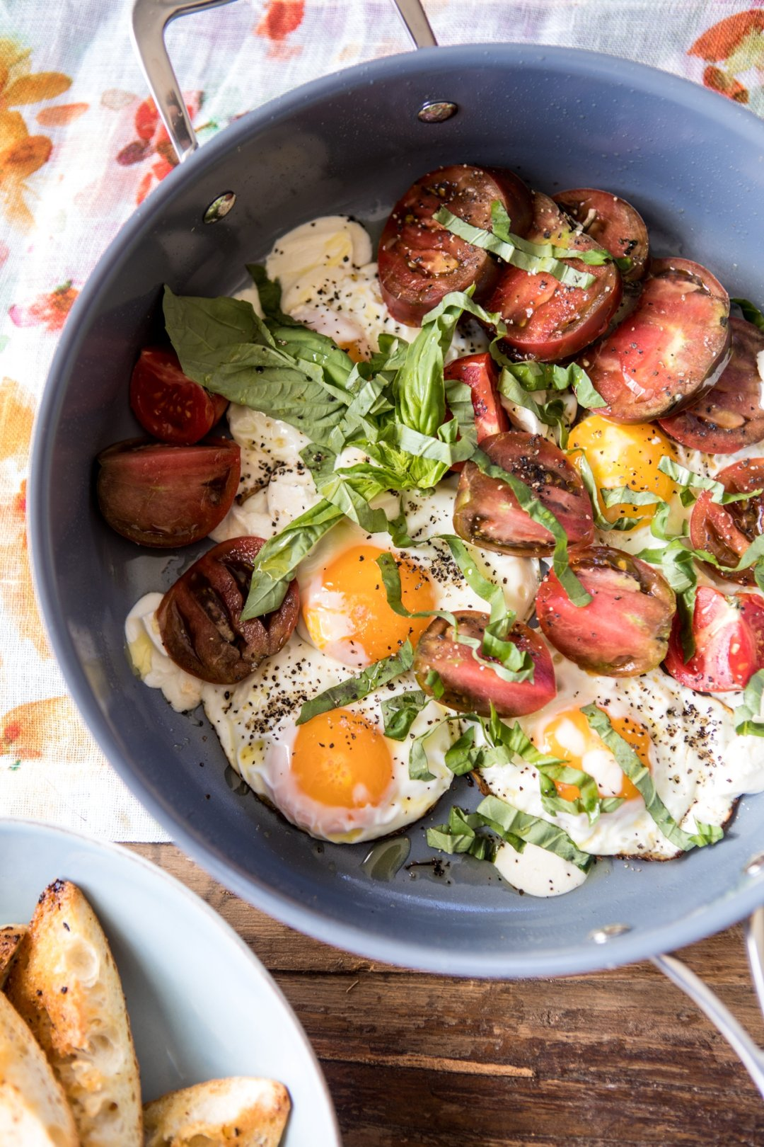 Pan with eggs and tomatoes and green herbs