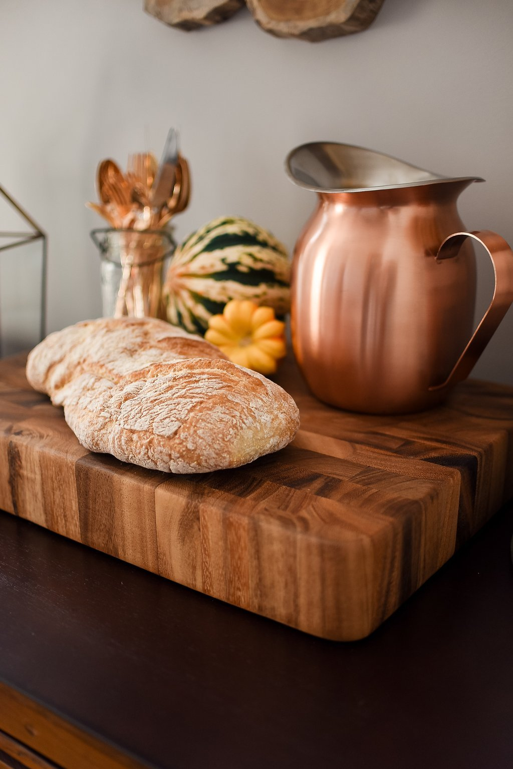 A fresh loaf of bread next to a copper pitcher on a wood serving platter
