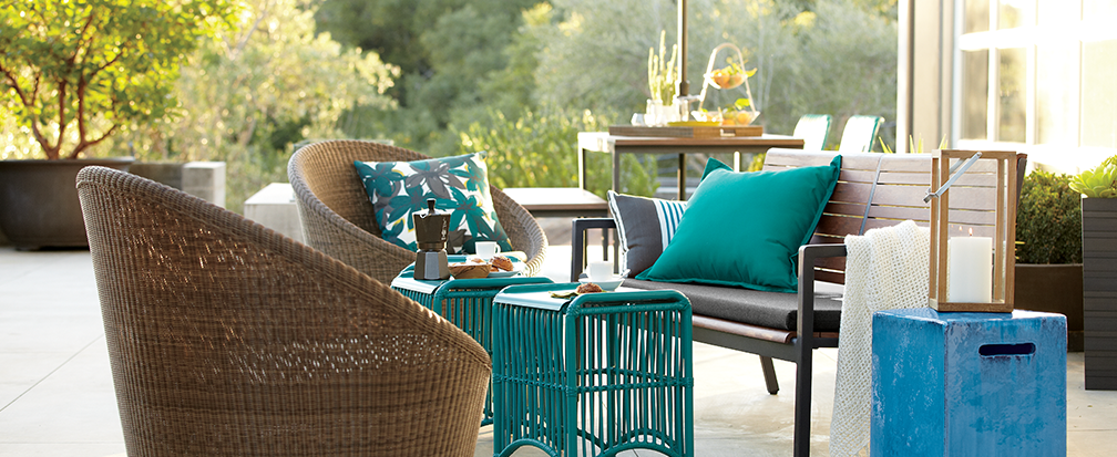 Backyard patio furniture with wicker chairs and aqua accents and pillows with an outdoor lanten on a table