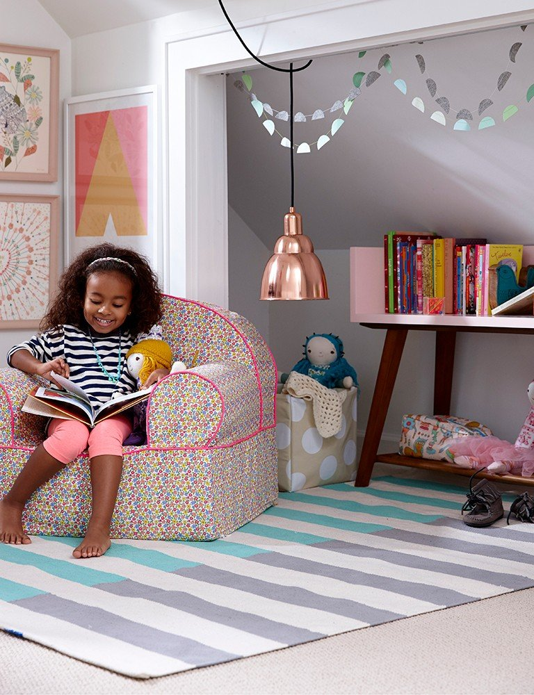 A young girl reads a book in a small, corner reading nook.