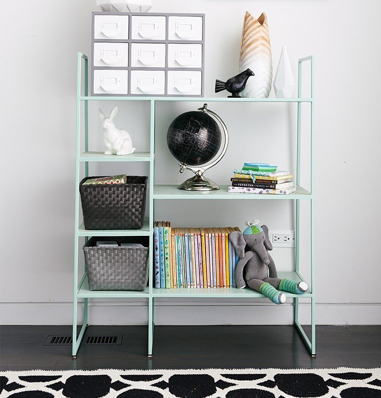 A sophisticated metal bookcase stores kids toys in a dining room