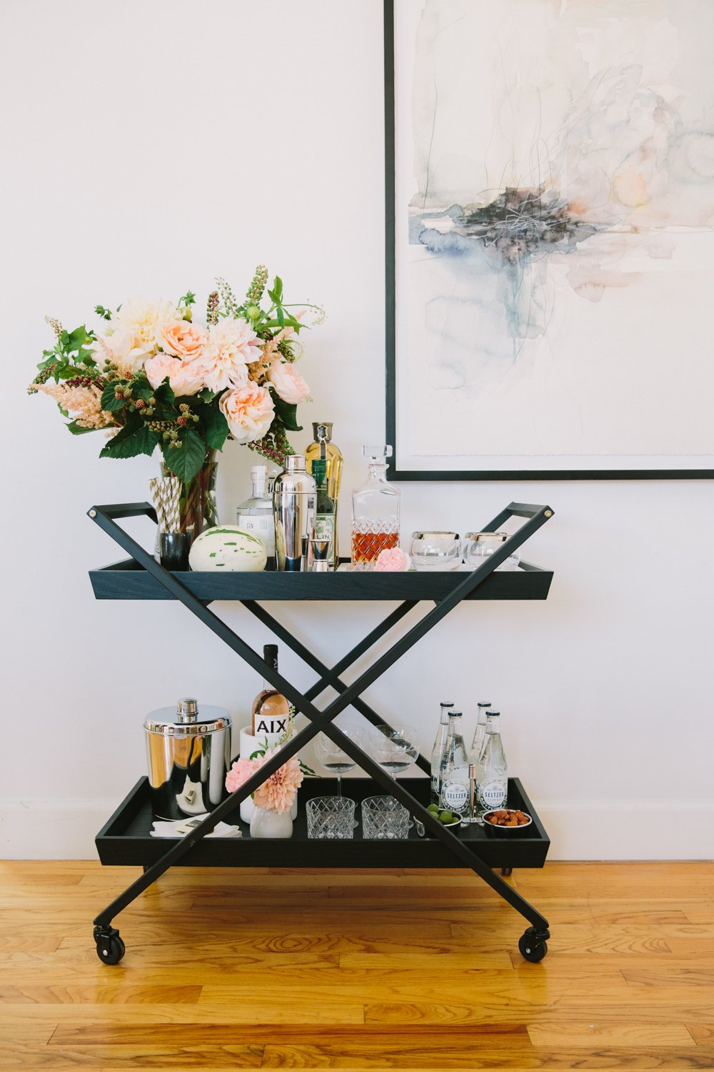 Stocked and decorated black barcart on casters in front of a hanging wall painting