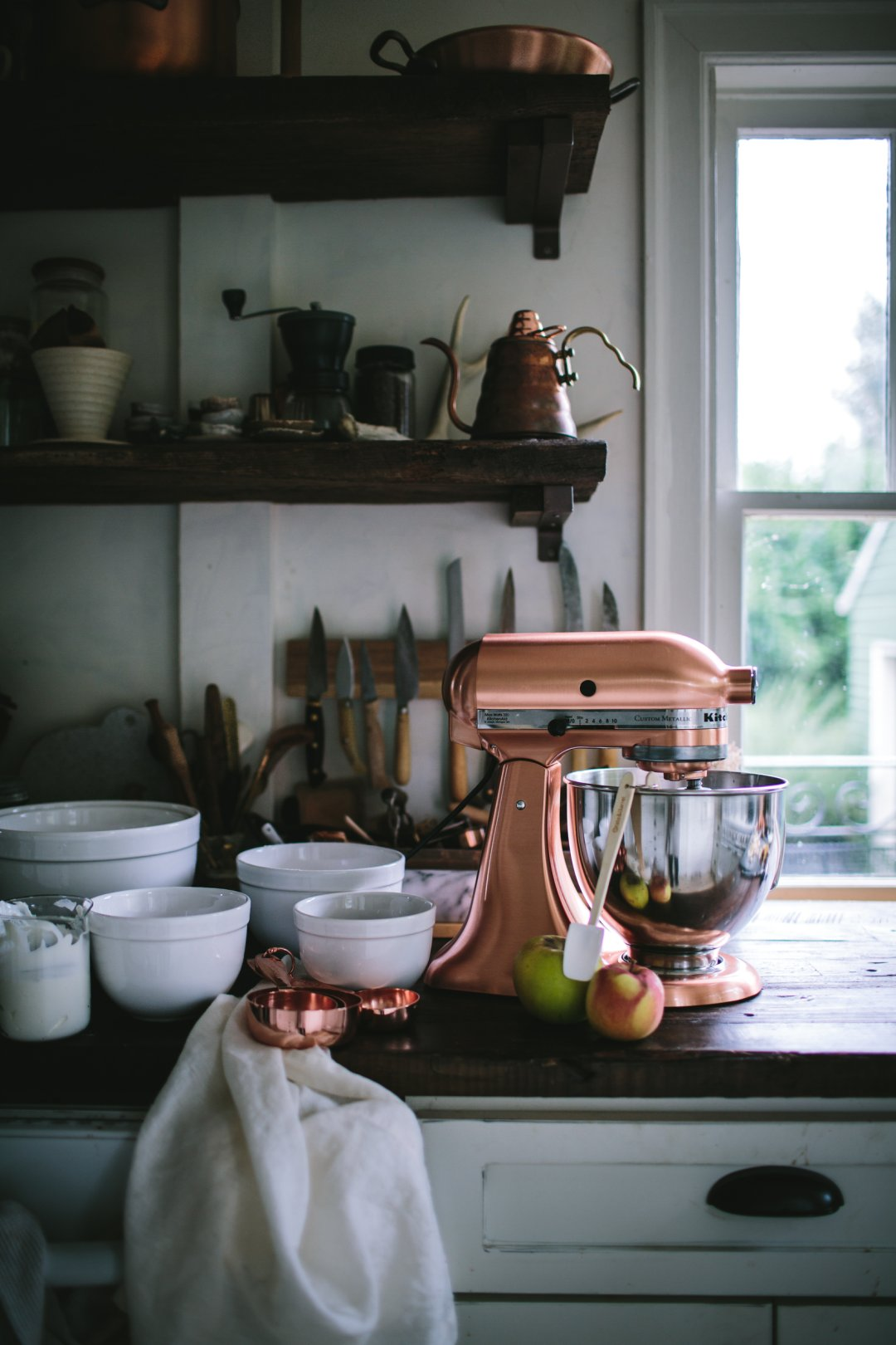 Copper KitchenAid stand mixer surrounded by mixing bowls, measuring cups and other prep ingredients