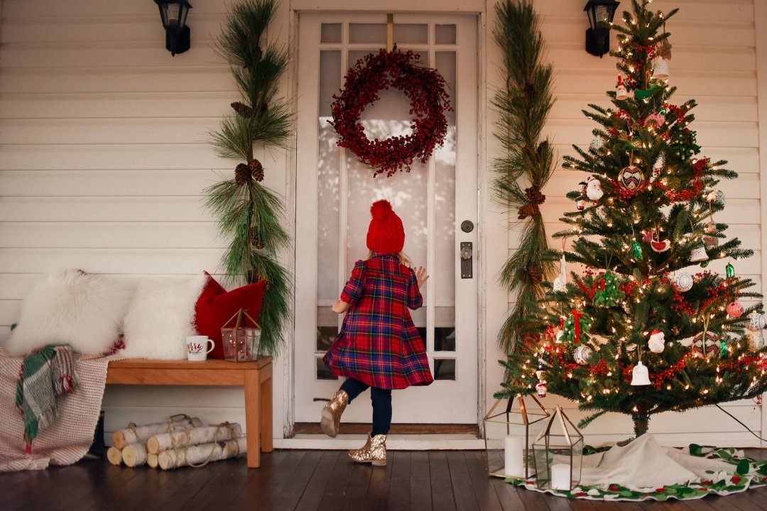 Little girl standing by a Christmas tree decorated with ornaments, red garland and string lights on a Christmas-themed front porch