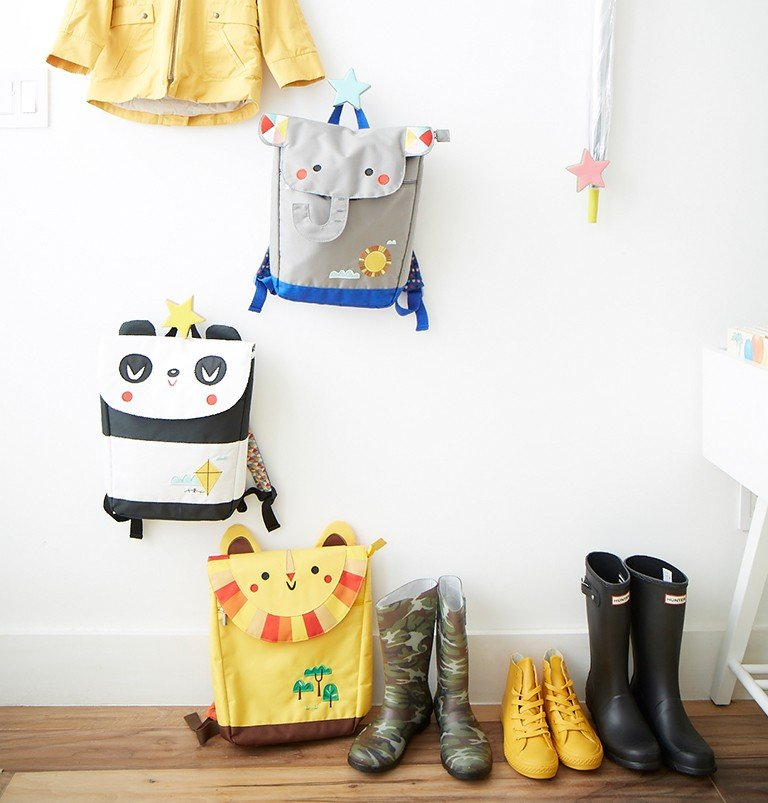 An entryway with wall hooks stores kids backpacks
