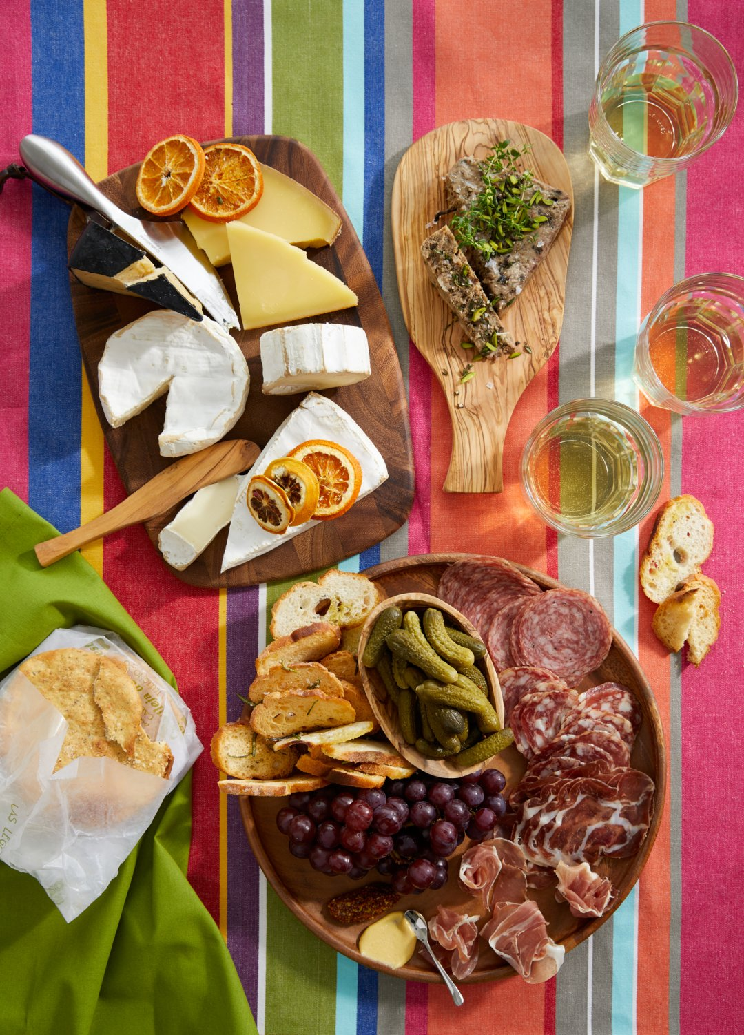 Cheese and charcuterie boards on a brightly colored striped tablecloth