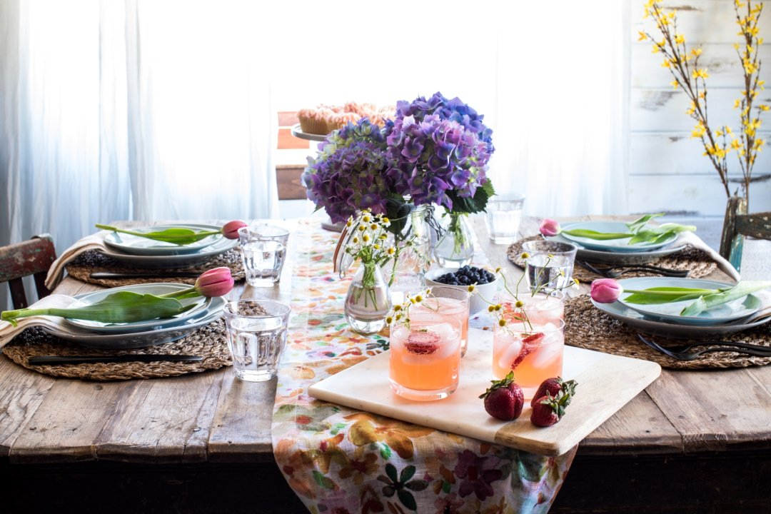 Full view of brunch table with floral tablerunner and place settings, along with food and drinks