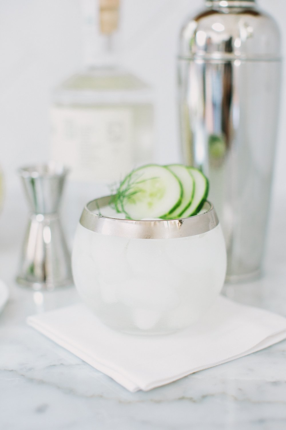 Short cocktail garnished with mint and cucumber on a marble surface
