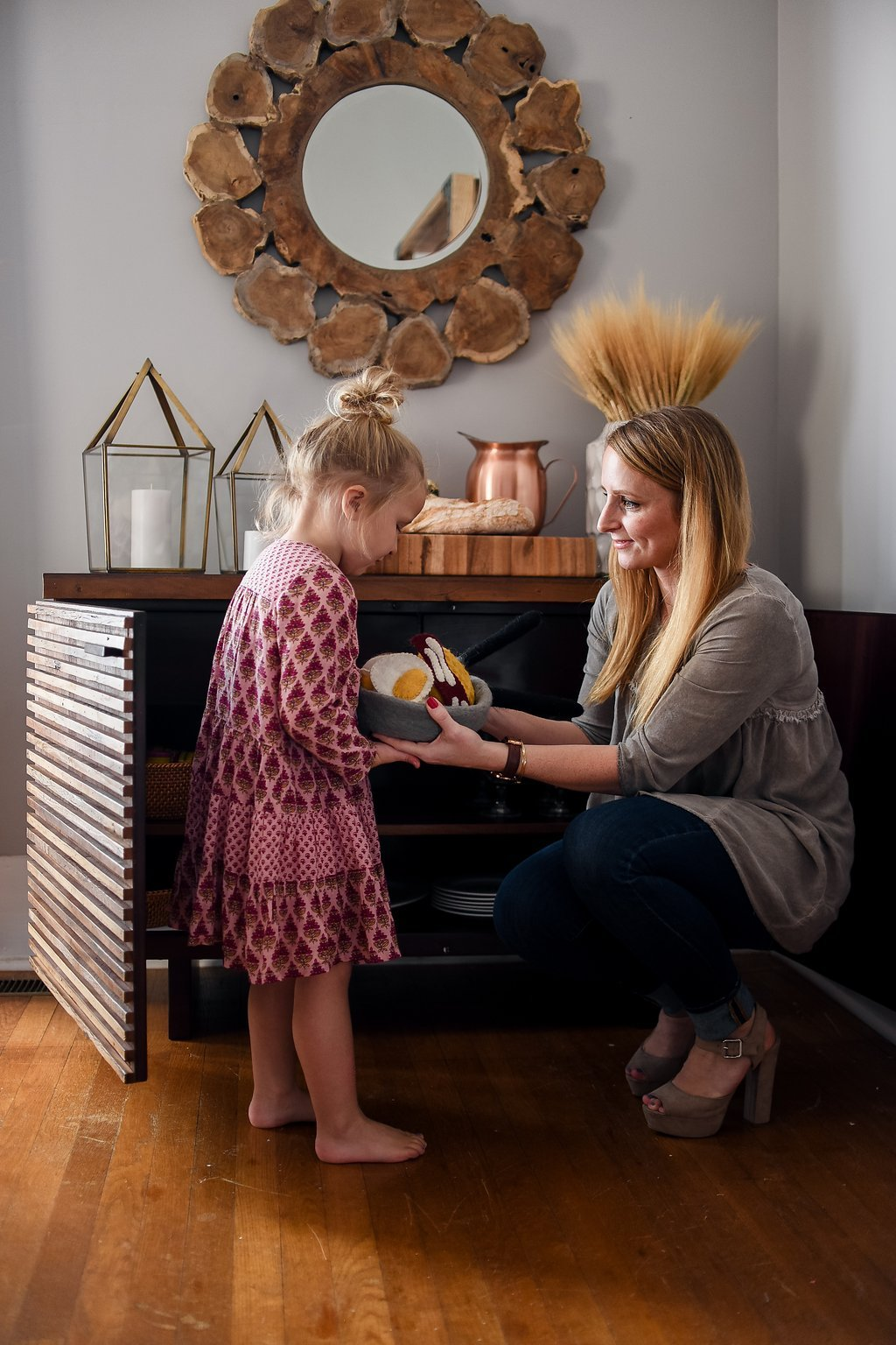 Mother and daughter opening sideboard to gather dinnerware and flatware