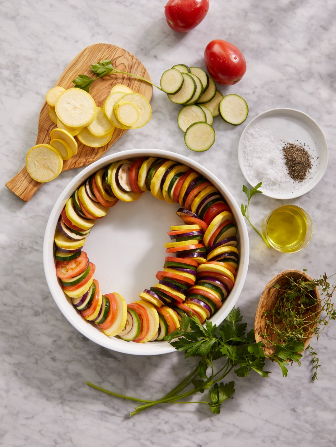 Thin sliced vegetables being placed in a round baking dish to make ratatouille