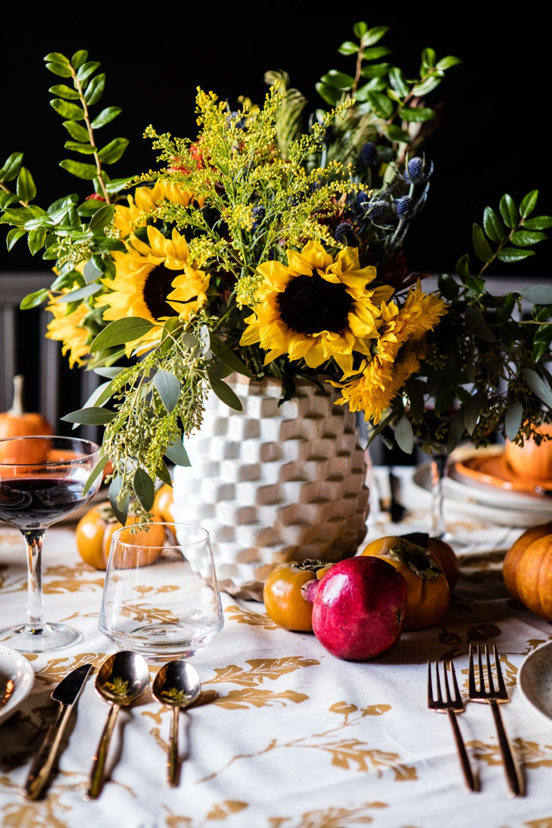 Centerpiece bouquet of green botanicals and sunflowers in a textured white vase