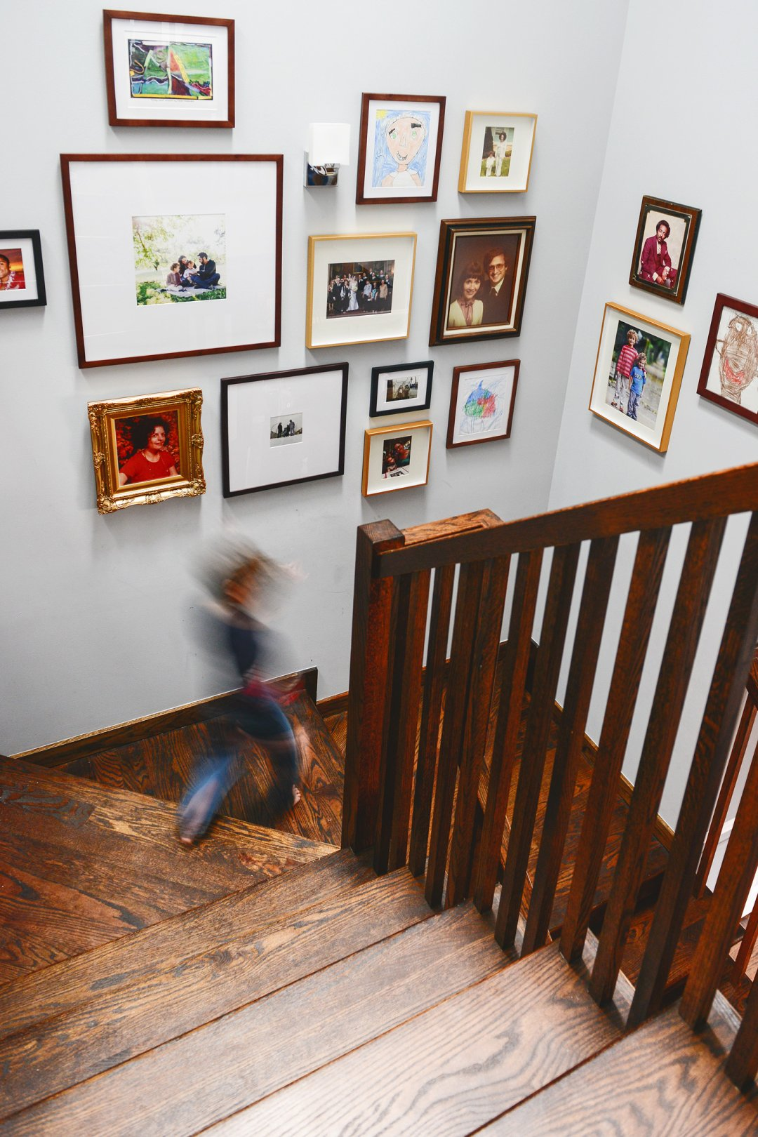 Boy walking down the stairs in front of photo wall