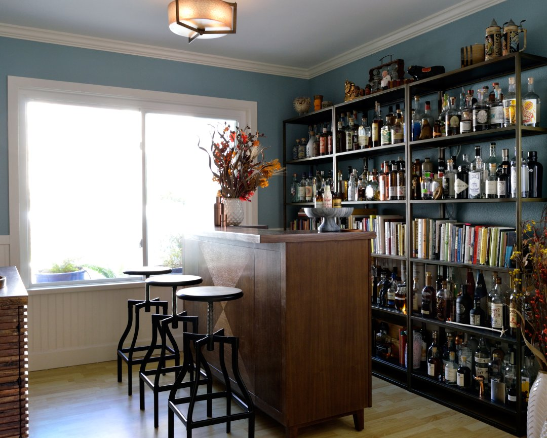 Three metal bar stools in front of a wood bar in front of an extensive shelving system of liquor bottles and hardcover books
