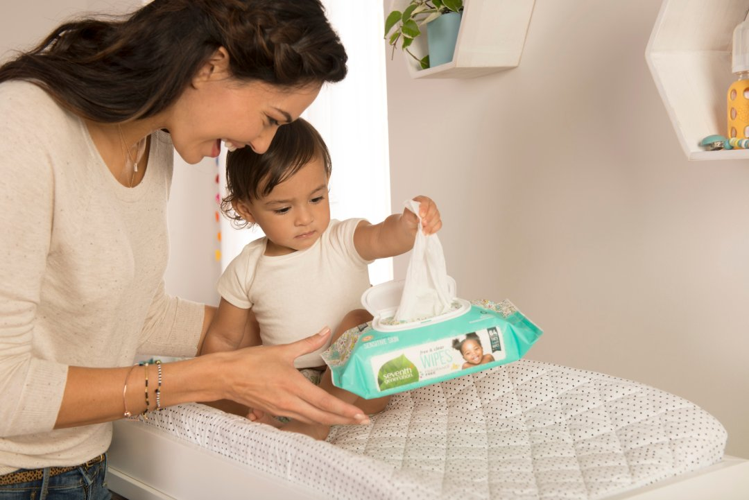 mom and baby in nursery, baby is pulling out a baby wipe