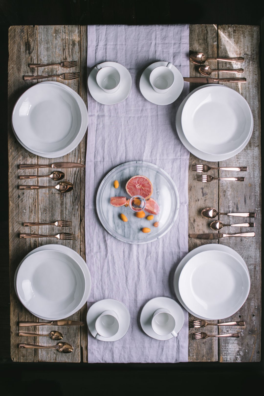 Overhead view of table set with white dinnerware, gold flatware, and a light purple table runner