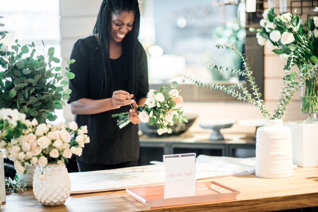 Woman arranging floral wedding bouquet