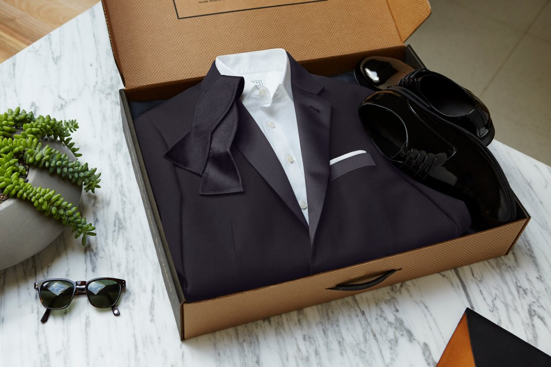 Open box displaying suit with bow tie and shoes, with sunglasses lying next to it