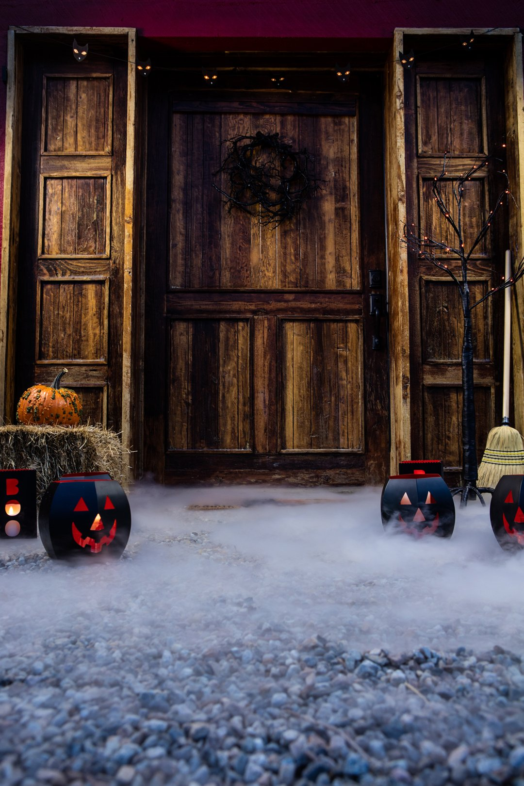 Path and doorstep decorating with jack'o'lantern lanterns and a haybale