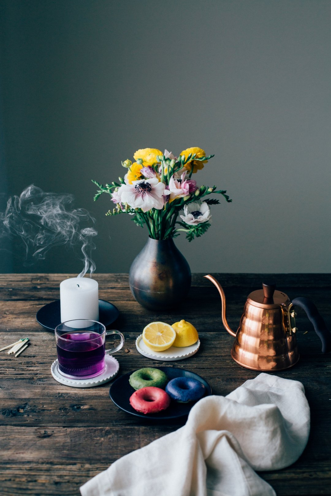 Vase with flowers, copper kettle, tea, and donuts