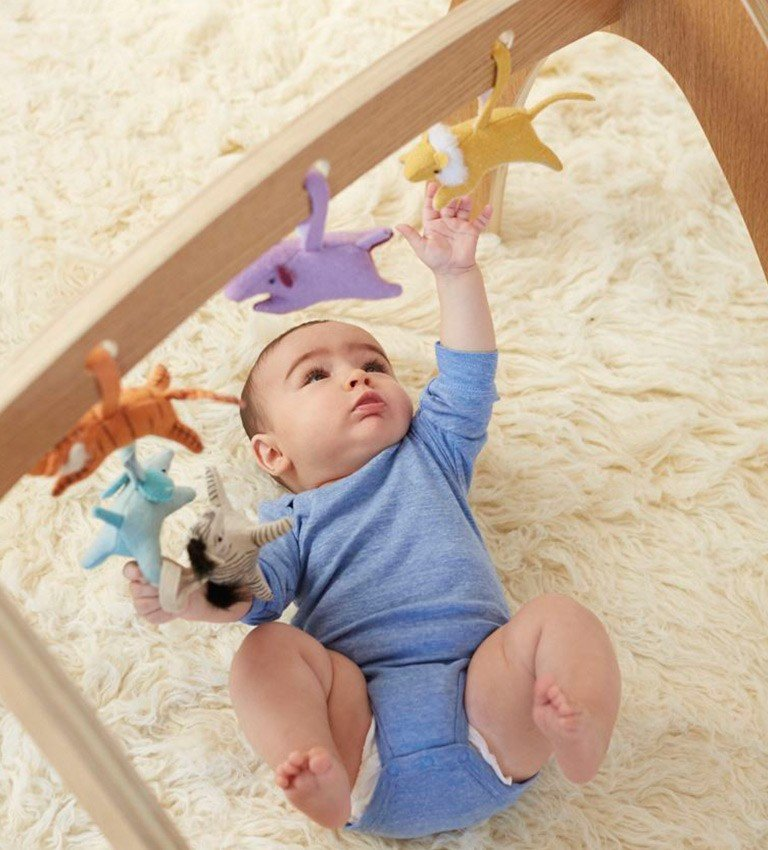 A one year old baby plays with rattles hanging from a wooden baby gym.