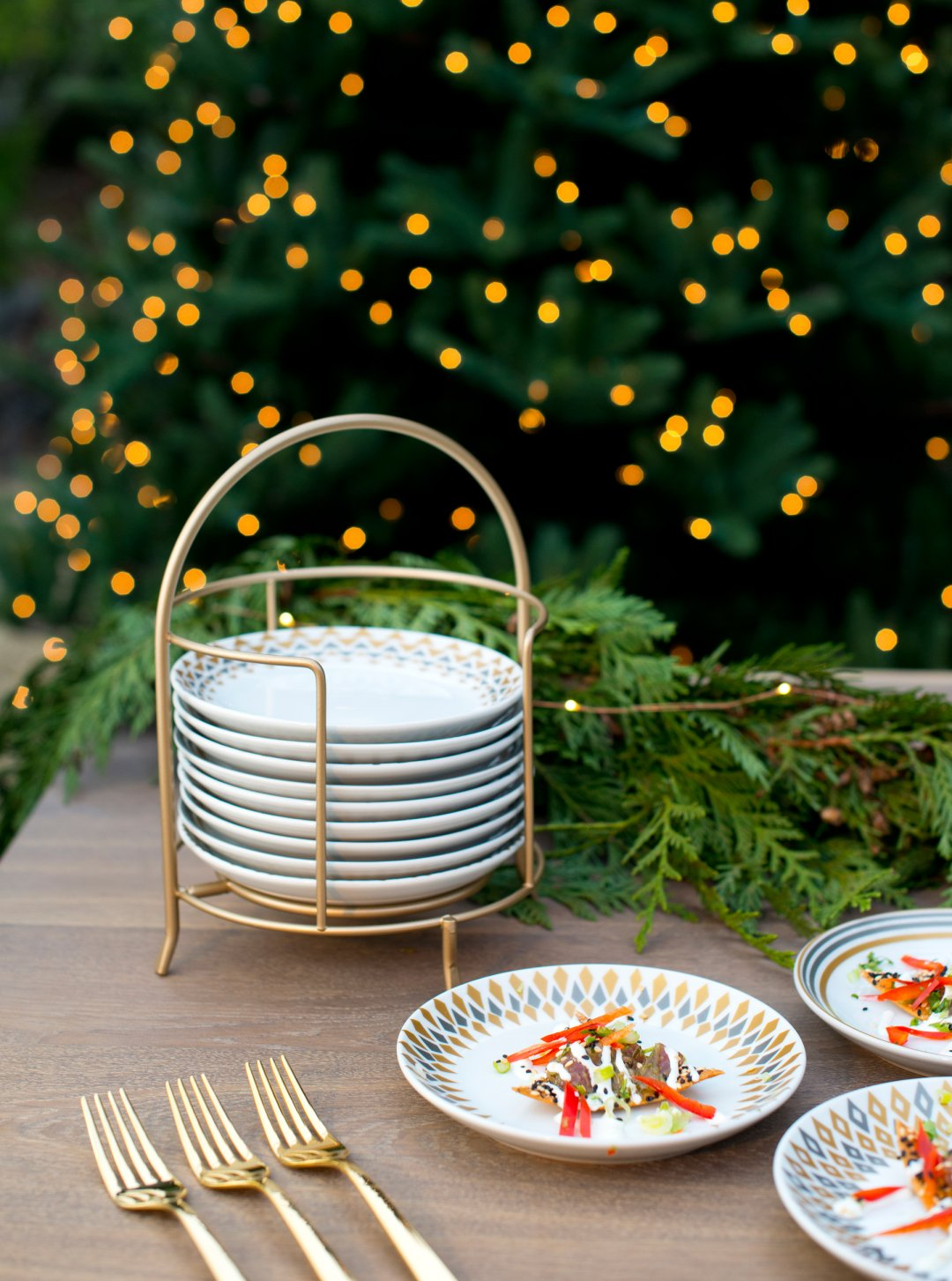 stack of plates in a rack sits near three forks and plates with food in front of a christmas tree