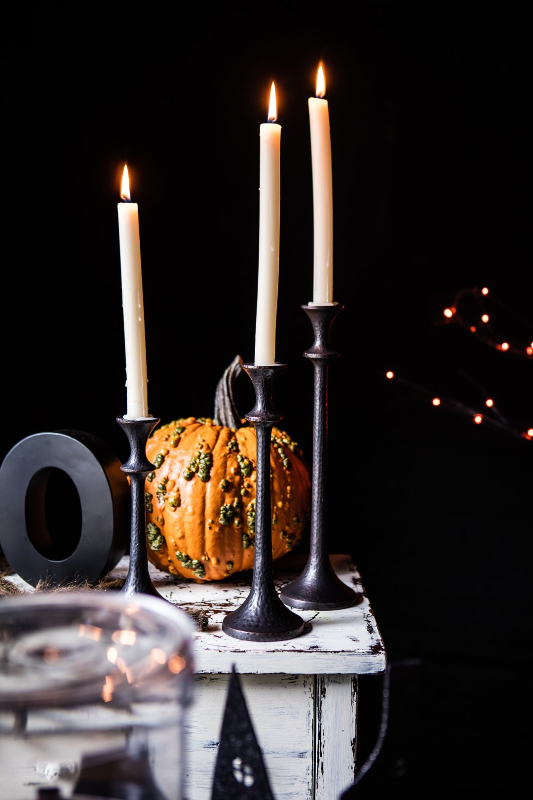 Tall, dripping taper candles on black candle holders