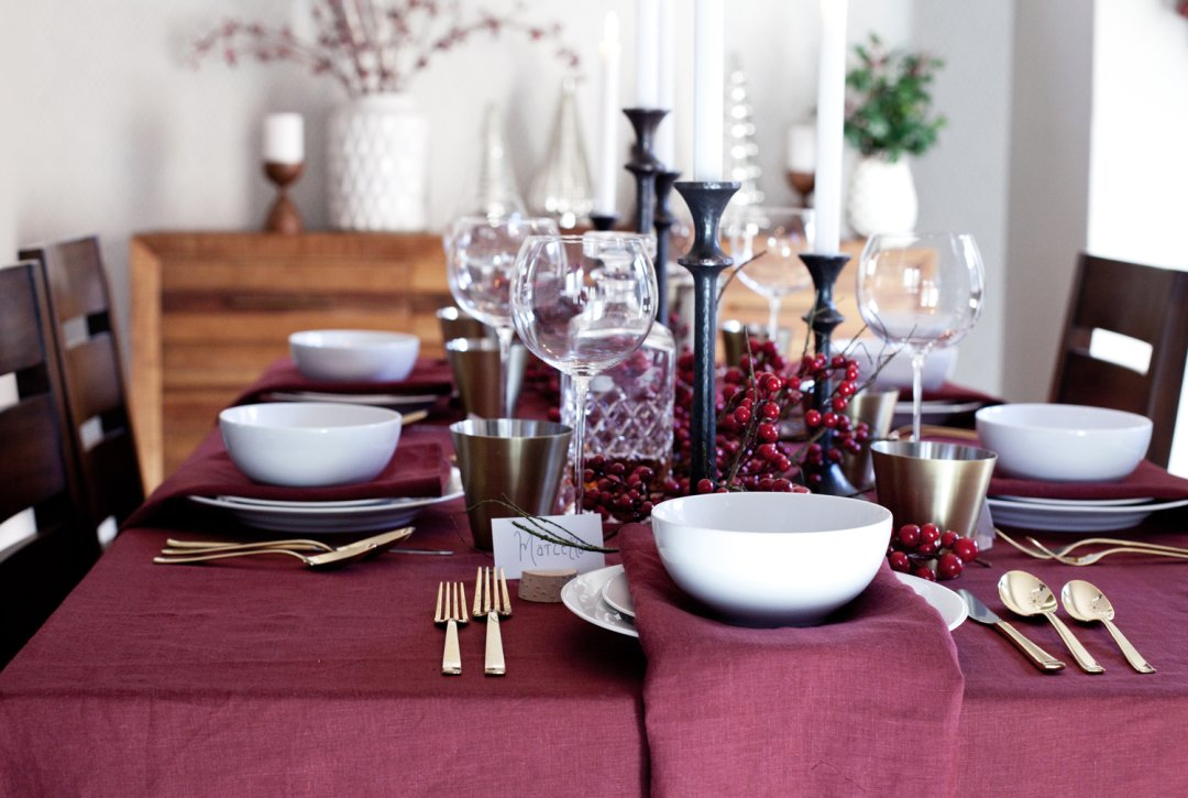 Maroon Christmas table set with white dinner ware and gold flatware