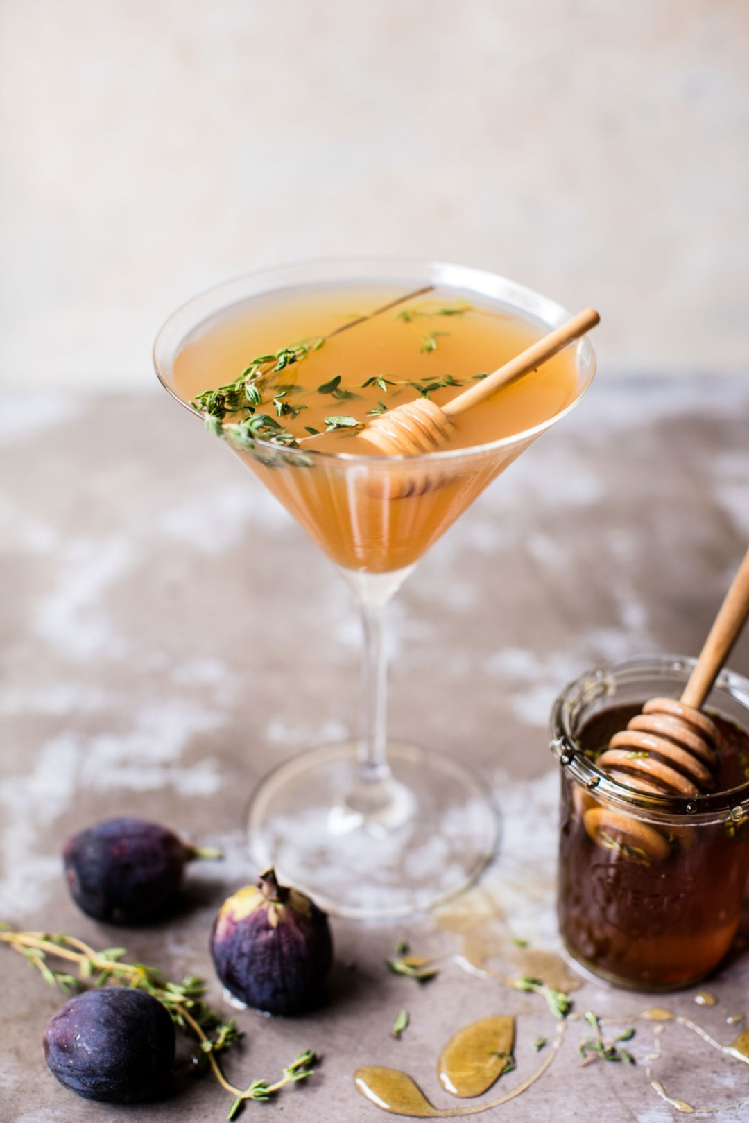 Honey and fig martini garnished with fresh thyme next to a glass honey jar and three fresh figs