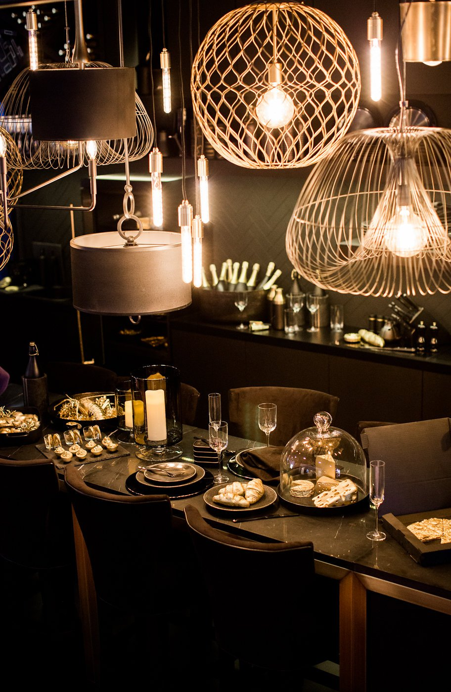Glimpse at table with golden food and pendant lighting in gold
