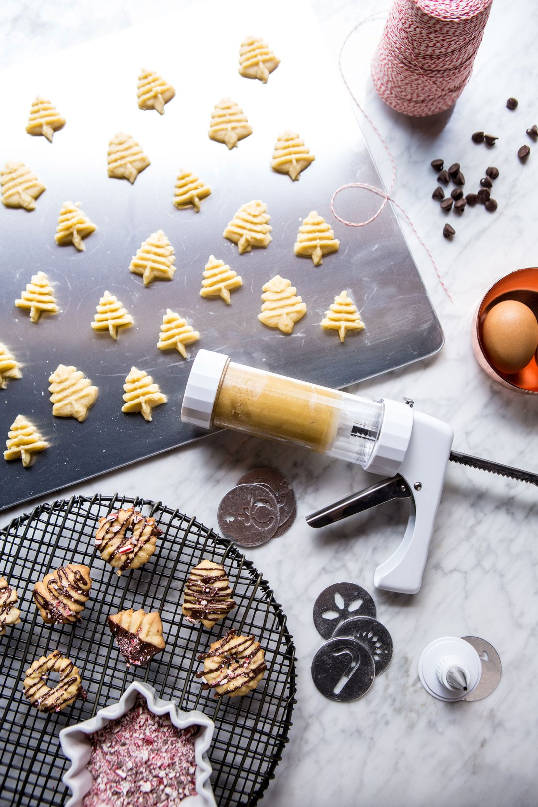 Raw sugar cookie dough in the shape of miniature christmas trees on a baking sheet next to a cookie press