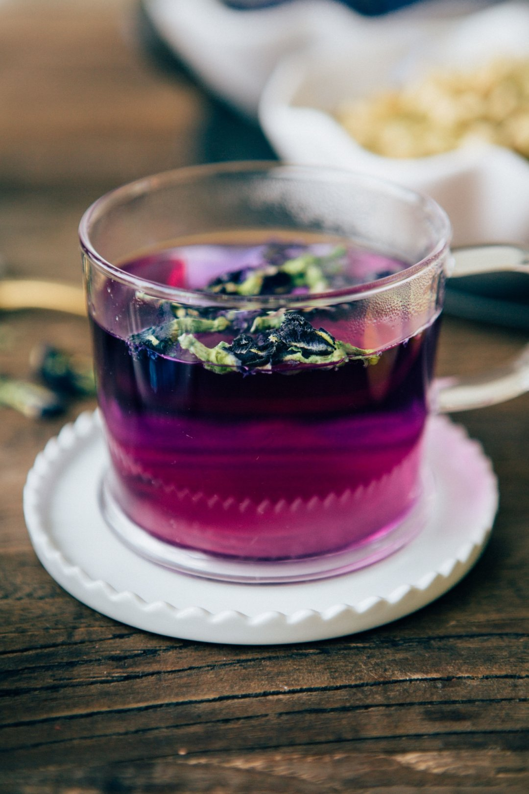 Glass cup of magenta tea on white saucer