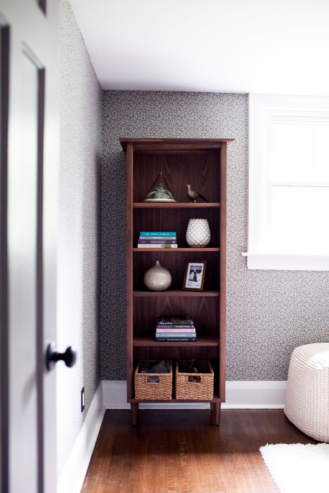 Bookcase filled with vases, books, and storage baskets