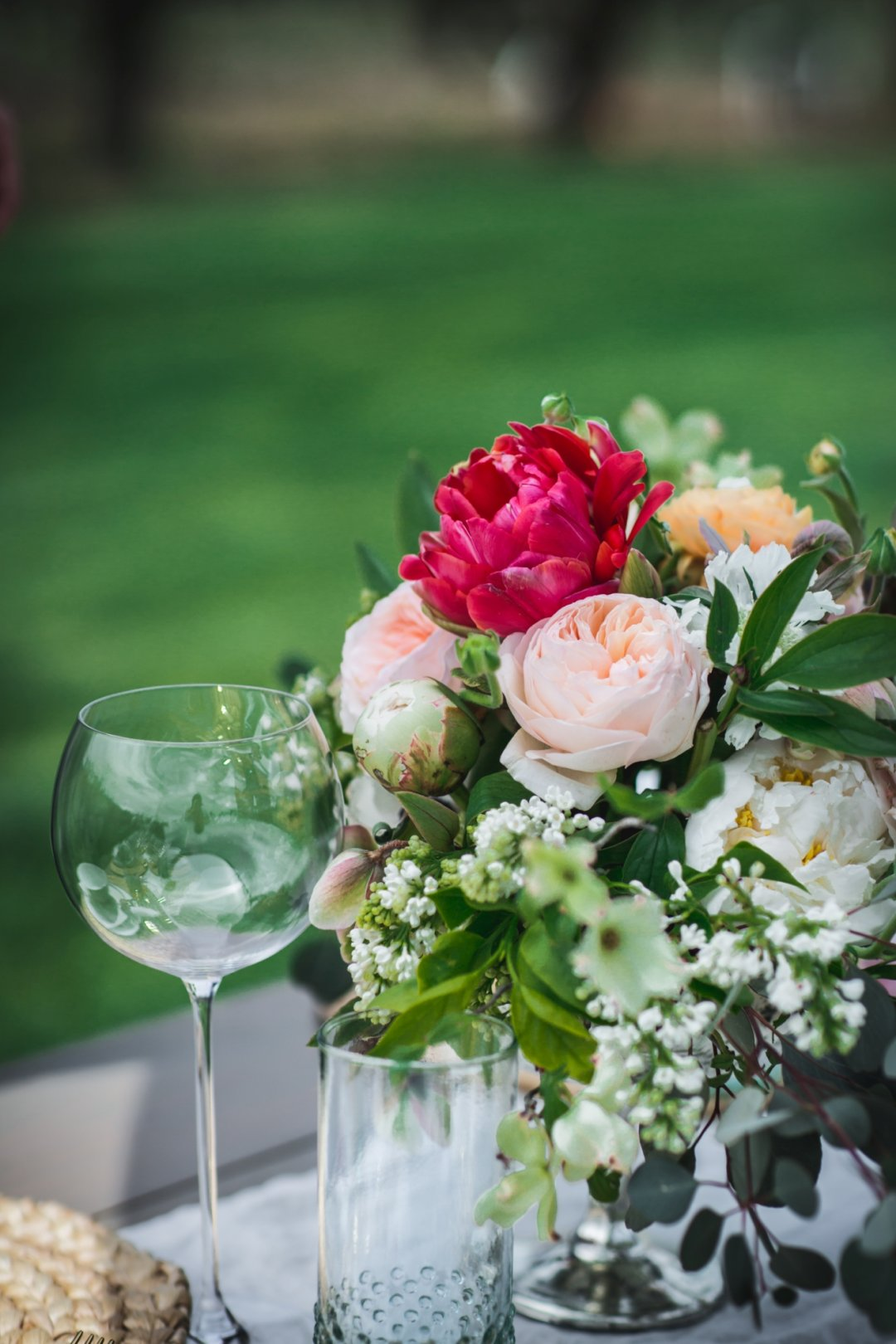 Wine glass and drinking glass next to centerpiece of flowers